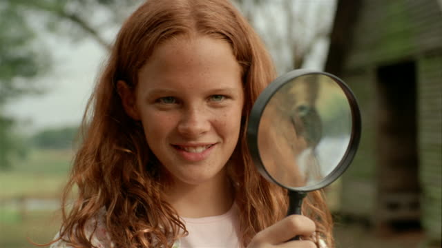 stockvideo's en b-roll-footage met close up portrait of girl holding magnifying in front of her face to magnify her features - vergrootglas