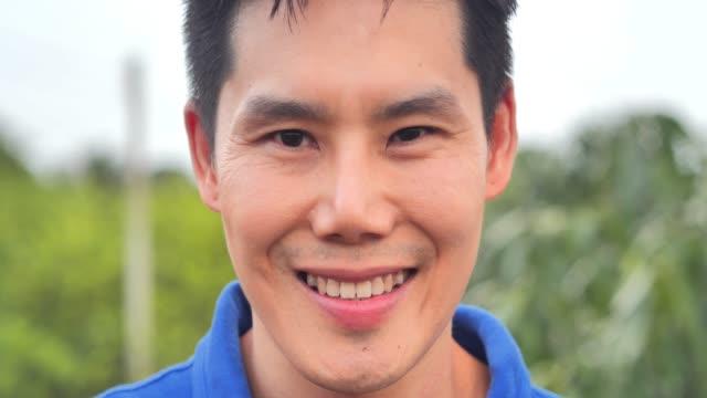 vídeos de stock, filmes e b-roll de feche acima do retrato do chinês novo considerável do asian do homem novo. considerável, face japonesa. homem de sorriso e esperto. conceito de ásia. - personas de negocios