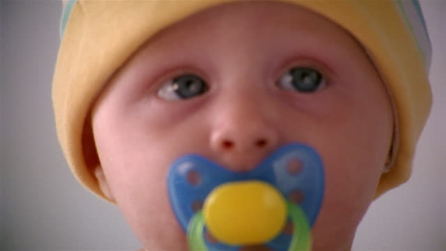 close up portrait of infant wearing hat and sucking on pacificer - sucking stock videos & royalty-free footage