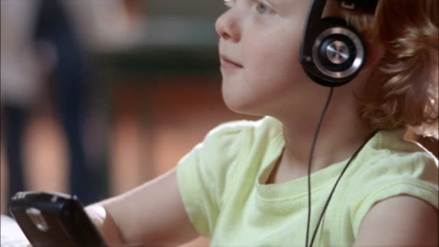 close up portrait of little girl wearing headphones and nodding her head to the music - stereo personale video stock e b–roll
