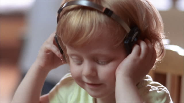 close up portrait of little girl wearing headphones and smiling - lyssna bildbanksvideor och videomaterial från bakom kulisserna