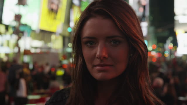 close up portrait of serious young woman in times square at night / new york city, new york, united states - nur junge frauen stock-videos und b-roll-filmmaterial