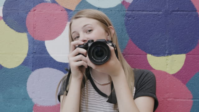 vídeos de stock e filmes b-roll de close up portrait of smiling girl photographing with camera near dotted wall / provo, utah, united states - provo
