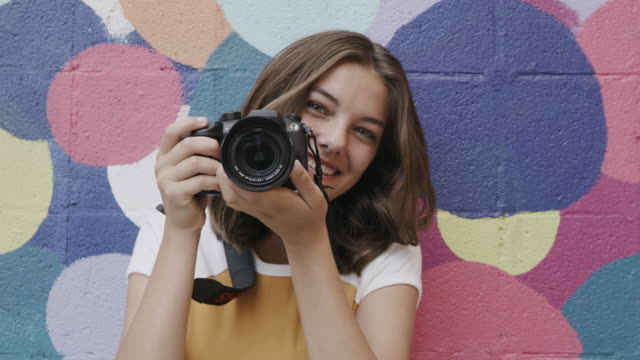 close up portrait of smiling girl photographing with camera near dotted wall / provo, utah, united states - fotograf bildbanksvideor och videomaterial från bakom kulisserna