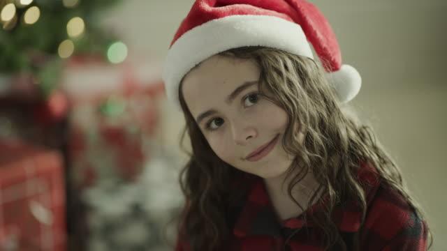 close up portrait of smiling girl wearing santa hat on christmas / orem, utah, united states - orem bildbanksvideor och videomaterial från bakom kulisserna