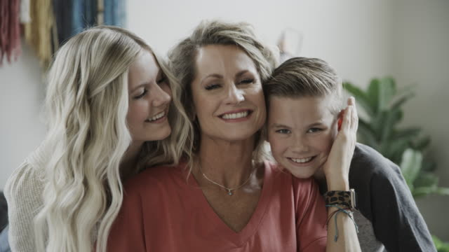 close up portrait of smiling mother cheek to cheek with son and daughter / lindon, utah, united states - cheek to cheek stock videos & royalty-free footage