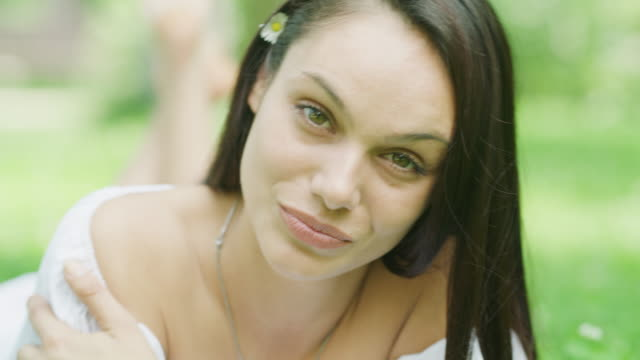 close up portrait of smiling woman laying in grass / kazanluk, bulgaria - legs crossed at ankle stock videos and b-roll footage
