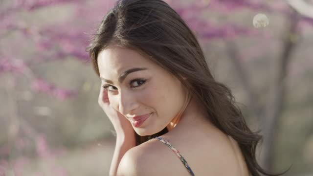 vídeos de stock, filmes e b-roll de close up portrait of smiling woman standing near flowering trees / cedar hills, utah, united states - mãos cobrindo boca