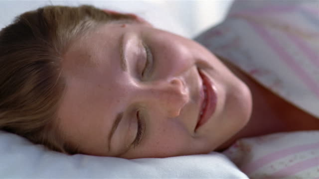 Close up portrait of smiling young woman rolling over and lying on pillow with eyes closed
