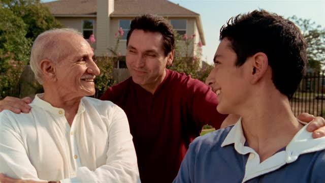 vídeos y material grabado en eventos de stock de close up portrait of three generations of men (grandfather, father and son) standing in yard - familia con un hijo