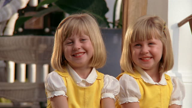 close up portrait of twin girls / smiling at cam and putting arms around each other / miami, florida - twin stock videos & royalty-free footage