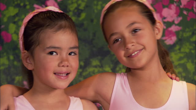 close up portrait of two ballerinas embracing and smiling - kind im grundschulalter stock-videos und b-roll-filmmaterial