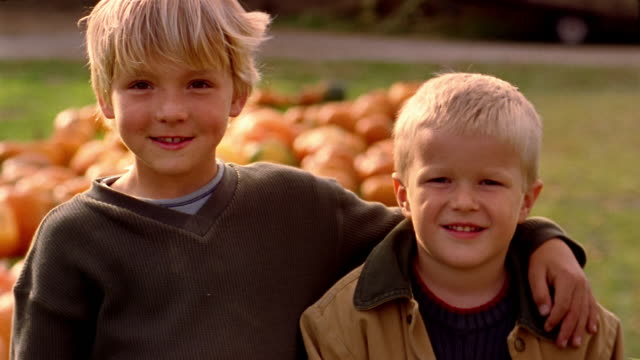 Close up portrait of two boys with pumpkins in background