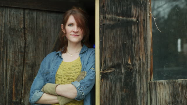 Close up portrait of woman leaning in doorway of rustic barn / Provo, Utah, United States