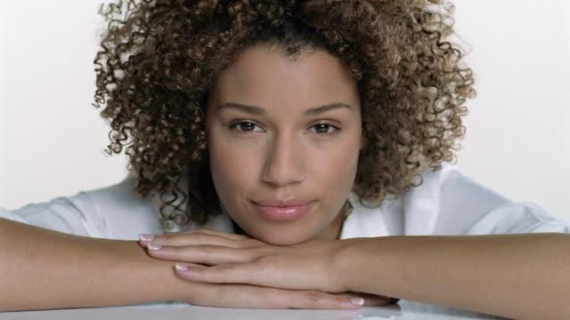 vidéos et rushes de close up portrait of woman resting chin on hands and smiling at cam - cheveux frisés