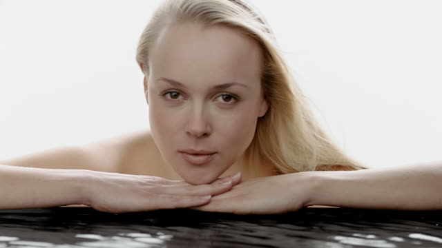 close up portrait of woman resting her head on edge of pool of water / raising her head and looking at cam - plain background stock videos & royalty-free footage