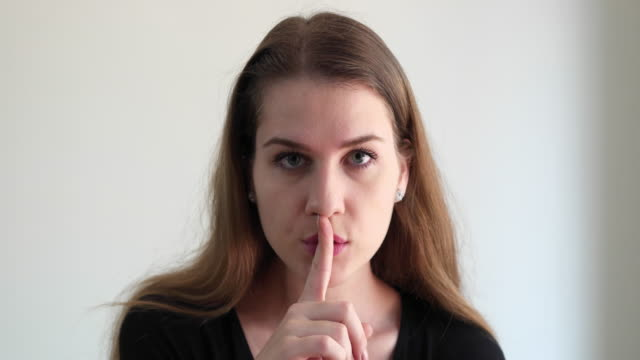 Close up portrait of woman with a finger on her lips asking to be quiet