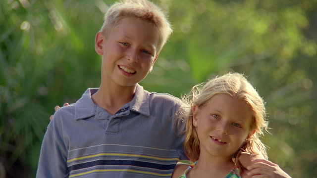 close up portrait of young boy and girl embracing + smiling at cam / miami, florida - sister stock videos and b-roll footage