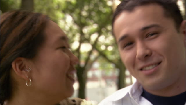 close up portrait of young couple leaning into each other and smiling at cam - video ritratto video stock e b–roll