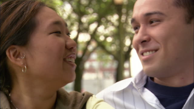 Close up portrait of young couple smiling at CAM, talking and laughing