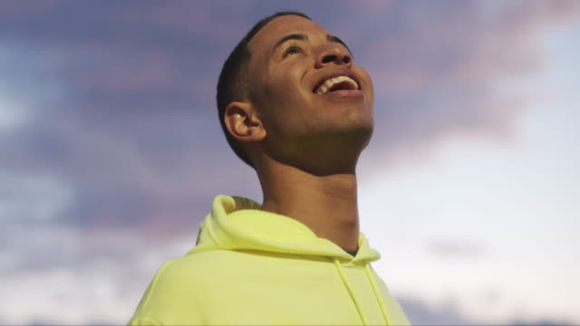 close up portrait of young man wearing a yellow hooded sweatshirt - single cloud sky stock videos & royalty-free footage
