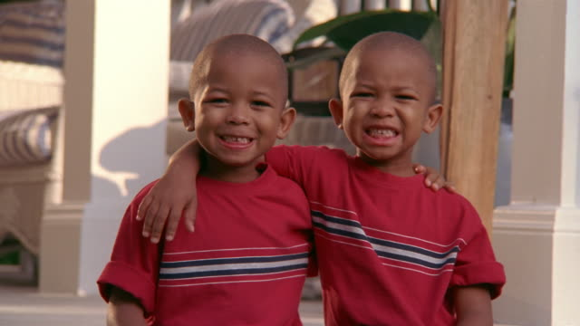 Close up portrait of young twin boys in matching outfits / smiling at CAM and looking at each other / Miami