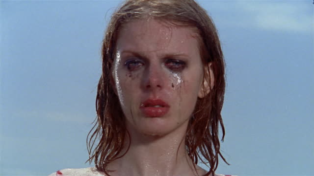 vidéos et rushes de close up portrait of young woman standing in rain with makeup running down her face - mascara