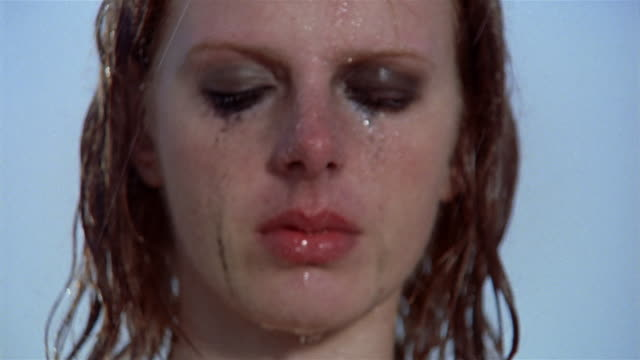 Close up portrait of young woman standing in rain with makeup running down her face / opening eyes