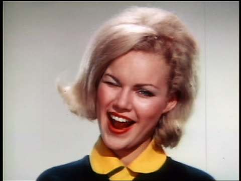 stockvideo's en b-roll-footage met 1966 close up portrait perky blonde cheerleader winking at camera in studio / industrial - knipogen activiteit