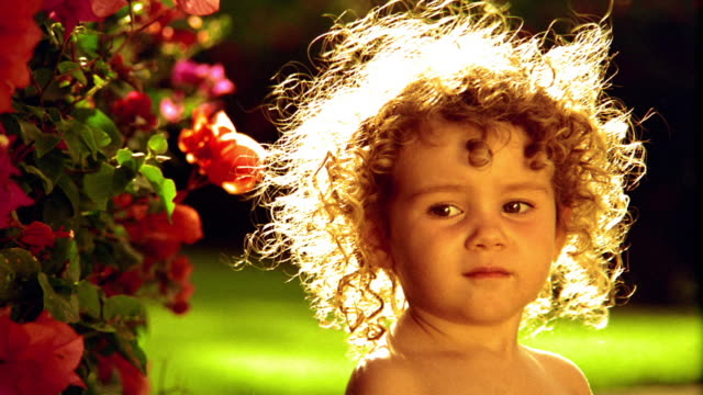 close up portrait profile girl toddler with curly hair in bright sunlight turning head to camera / hawaii - 女児1人点の映像素材/bロール