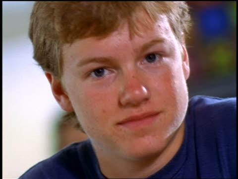stockvideo's en b-roll-footage met close up portrait redhead/blonde teen boy looking down then up at camera indoors - alleen één tienerjongen