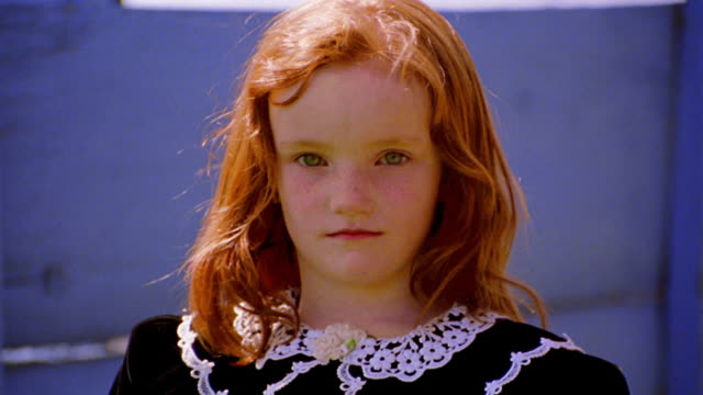 close up portrait redheaded girl in black dress looking somber outdoors / blue background - black dress stock videos & royalty-free footage