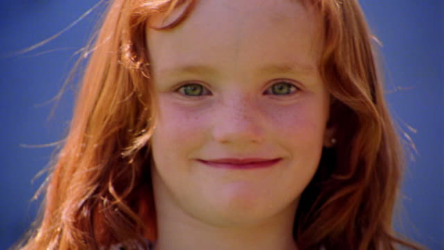 close up PORTRAIT redheaded girl smiling at camera outdoors / blue background