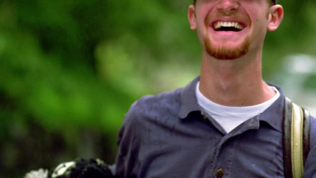 close up portrait red-headed man with beard in baseball cap, holding golf bag and laughing / california - baseball cap stock videos & royalty-free footage