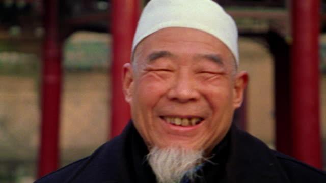 close up PORTRAIT senior Asian man with beard in cap smiling / Xi'an, China