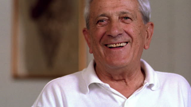 close up portrait senior italian man talking + laughing indoors / italy - italian culture stock-videos und b-roll-filmmaterial