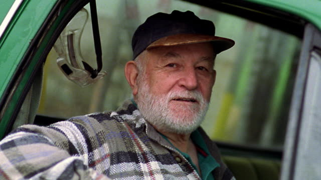 vídeos de stock, filmes e b-roll de close up portrait senior man with beard in baseball cap sitting in truck looking out window / california - olhando para a câmera