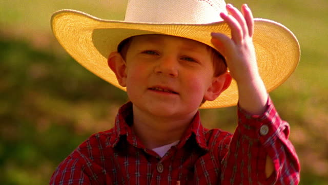 close up portrait small boy wearing + tipping straw cowboy hat outdoors - straw hat stock videos & royalty-free footage