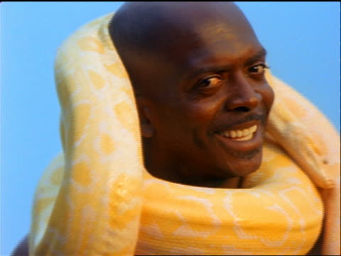 close up PORTRAIT smiling bald Black man with large yellow snake wrapped around his neck