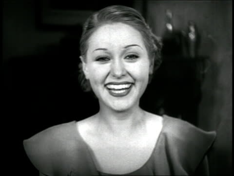 vidéos et rushes de b/w 1936 close up portrait stoned hispanic woman smoking + laughing (may be sara garcia) / feature - 1936