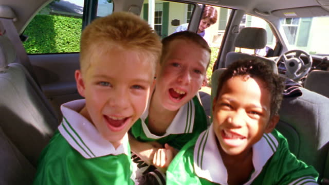 close up PORTRAIT three boys in soccer uniforms cheering + pumping fists in minivan with woman in background