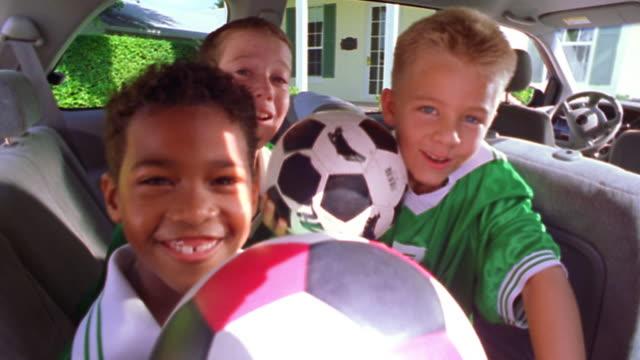close up PORTRAIT three boys in uniforms raising soccer balls towards camera in minivan / Florida