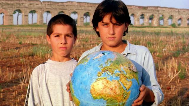 vídeos de stock, filmes e b-roll de close up portrait two boys holding globe with aqueduct in background / italy - cartografia