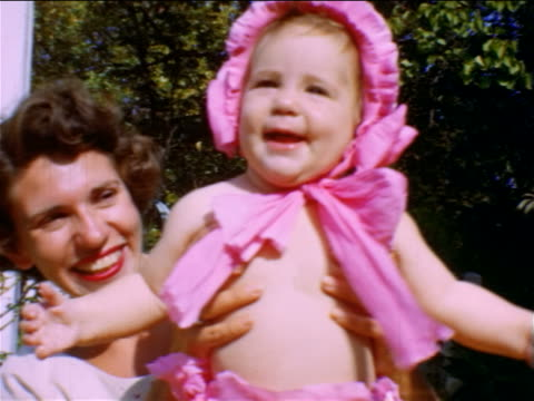vídeos de stock, filmes e b-roll de 1950 home movie close up portrait woman holding smiling baby with pink bonnet - rosa cor