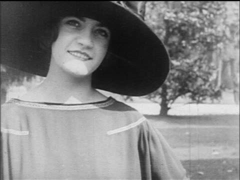 stockvideo's en b-roll-footage met b/w 1917 close up portrait woman in large-brimmed hat smiling at camera - 1917