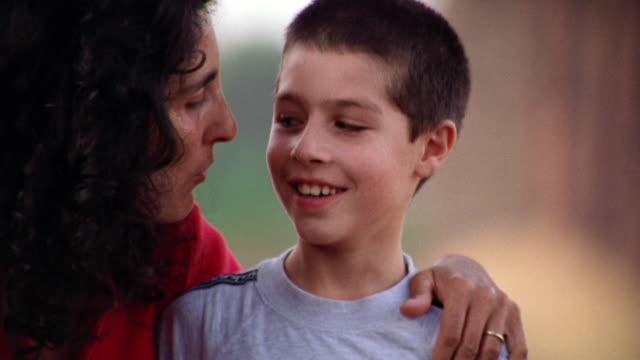 vídeos y material grabado en eventos de stock de close up portrait woman kissing boy on cheek + boy laughing outdoors / italy - familia con un hijo