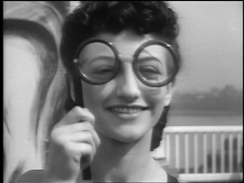 close up portrait woman lifts hand-held glasses in front of eyes / palisades park, nj / newsreel - palisades park stock videos & royalty-free footage