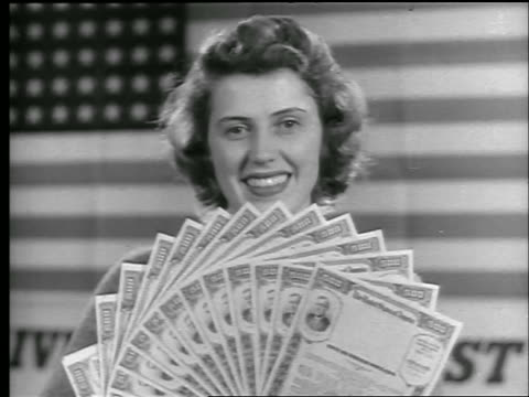b/w 1944 close up portrait woman smiling at camera holding up stack of war bonds / us flag in background / news - 1944 stock videos and b-roll footage