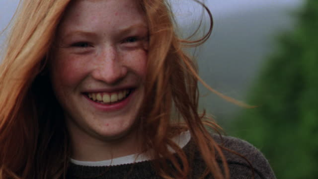 vidéos et rushes de close up portrait woman smiling, smoothing red hair in wind + tilting head / kilkenny county, ireland - irlande