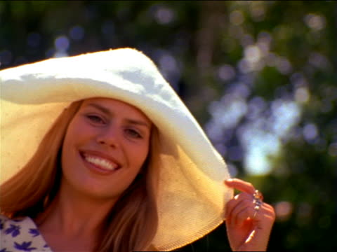 close up portrait woman with long blonde hair + floppy straw hat smiling at camera - straw hat stock videos & royalty-free footage
